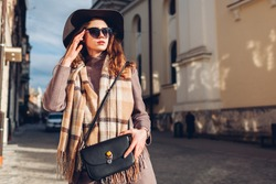 Street female fashion. Portrait of stylish young woman wearing hat glasses holding purse outdoors. Spring accessories