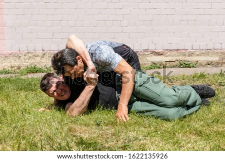 Street fight. The attacker is trying to apply strangulation. Rivals lie on the ground. Martial arts instructors demonstrate self-defense techniques of Krav Maga