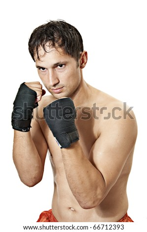 Street fighter holds hands clenched in fists before himself. Kickboxing or muay thai