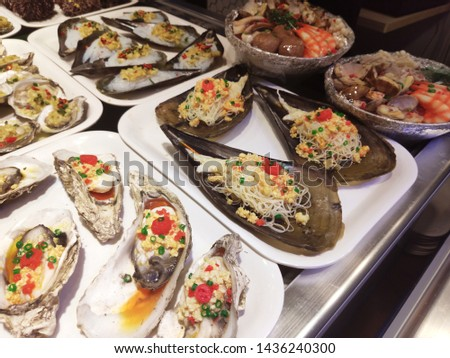 street food asian traditional sea oysters mussels shells with noodles on the shelves in a store on the Hainan island in the city of Sanya in China