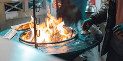 Street food.Burning Fire.Fried chicken meat,Shaverma,Doner kebab.The chef cooks the meat over an open fire.Closeup.Bonfire, burning trees logs.Ash and coal.Diner in the city,at the festival.Delicious.