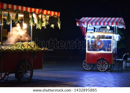 Street food carts in night with text on signboards in translation from Turkish language on English is Roasted chestnuts and corn. #1432895885
