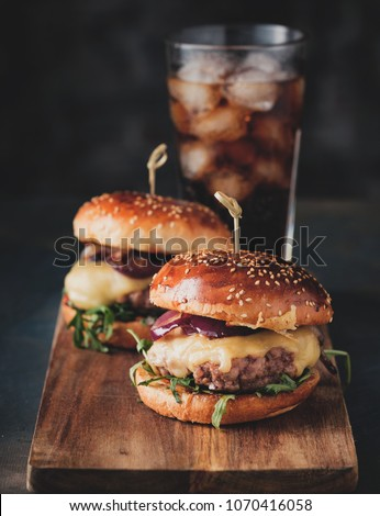 Street food, fast food. Homemade juicy burgers with beef, cheese and caramelized onions on the wooden table. Toned image.