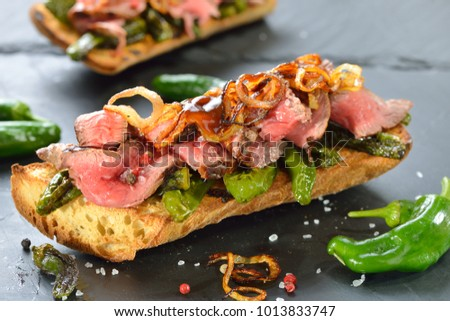 Shutterstock Street food: Hot Panini topped with fried pimientos, grilled beef steak, roasted onion rings and hot sauce