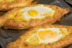 Street food in Ukraine -  Georgian khachapuri as traditional Adjarian version  bread  filled with cheese, butter and egg yolk in the middle