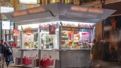 Street food kiosk and sausage stand night timelapse in Vienna. People buying food with drinks and eating around