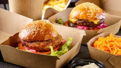 Street food. Meat cutlet burgers are in paper boxes. Food delivery.