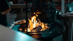 Street food. The chef prepares Shawarma, Doner kebab over an open fire. Burning Fire. Fried chicken meat, Closeup. Bonfire, burning trees logs.Ash and coal.Diner in the city,at the festival.Delicious.