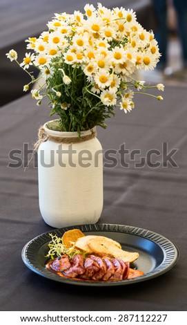 Street food: tuna steak with daisy flower bouquet
