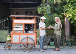 street food vendor handing a bowl of bakso or meatball to customer