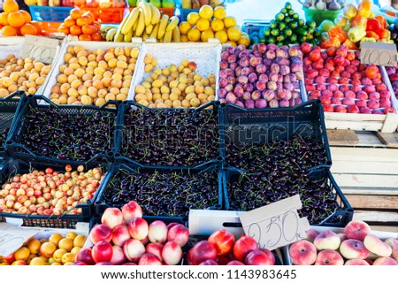 Street fruit and vegetable store counter with crates. Crates of cherry, cherries, plum, apricot, banana, cucumber. Heap of berries. Trade tent. #1143983645