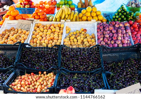 Street fruit and vegetable store counter with crates. Crates of cherry, cherries, plum, apricot, banana, cucumber. Heap of berries. Trade tent. #1144766162