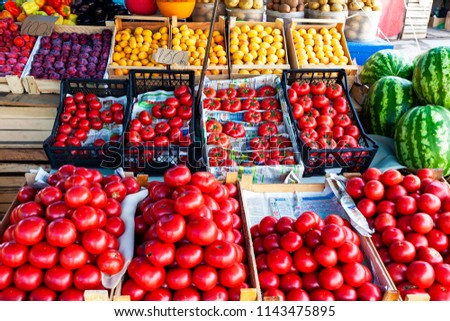 Street fruit and vegetable store counter with crates. Crates of tomato, plum, apricot, watermelon. Glare on tomatoes. Trade tent. #1143475895
