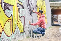 Street graffiti artist painting with a color spray can a dark monster skull graffiti on the wall in the city outdoor - Urban, lifestyle contemporary street art concept - Main focus on his hand