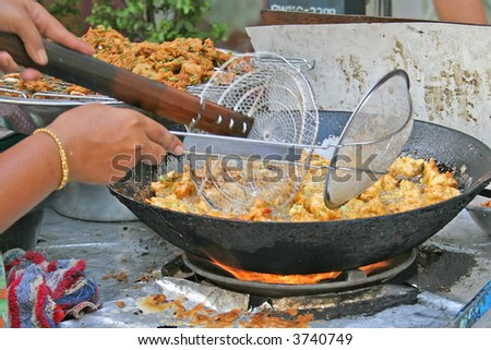 Street Hawker in Bangkok selling spicy fried fishcakes