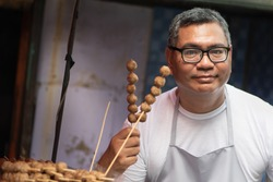 street hawker man working with his delicious meatball skewer street food; concept of asian street food, tourism with local food, small business, meal vendor, street food hawker