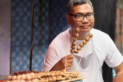 street hawker man working with his delicious meatball skewer street food; concept of asian street food, tourism with local food, small business, street food hawker