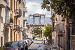 Street in Athens overlooking the ancient Hadrian's Gate or Arch of Hadrian, Greece. It is a landmark of Athens. View of historical district in the Athens city. Old architecture of the Athens center.
