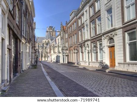 Street in Dutch town of Dordrecht. Grote Kerk Church in the distance.