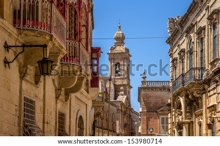 Street in Mdina full of balconies and the Carmelite convent in the end of the street.