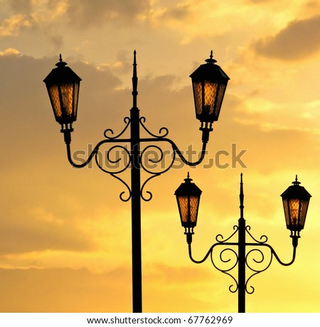 Street lamp of retro style. Street light at sunset with cloudy sky. Two urban lantern in the park.