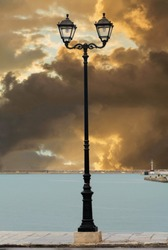 Street lamp of Zakynthos harbor Greece. Street lamp against dramatic sunset.