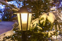 Street lamp.  Switched-on street lamp against decorated Christmas tree and garlands in the snow close up.