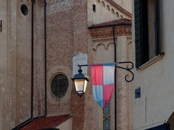 Street lamp with a flag on the wall of a house. Montagnana, ITALY