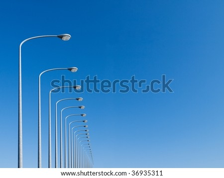 street lamps aligned with beautiful blue sky in background