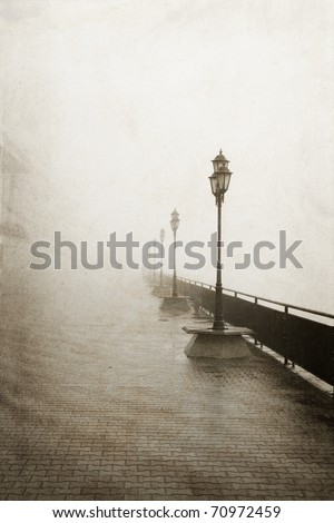 Street lamps in a fog. Photo in vintage image style.