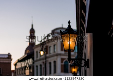Street lamps of Riga's old town being lit up as the sun starts to fade after the sunset