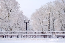 Street lantern with bench in snow - beautiful cold winter day in January Riga latvia