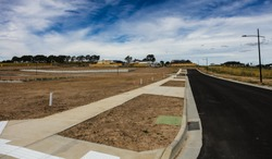 Street level looking at a newly created Australian housing estate. Roads and gutters have been built, Land about to be titled so owners can start building the great Australian dream, a family home.