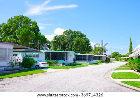 Street level view of a very well kept mobile home trailer park neighborhood in central Florida with nice yards and big green trees on a beautiful sunny afternoon