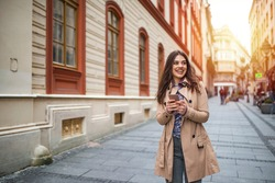 Street life. Business woman with phone on the street. Beautiful young woman with smart phone outdoors at sinlight. Beautiful city girl with smart phone.