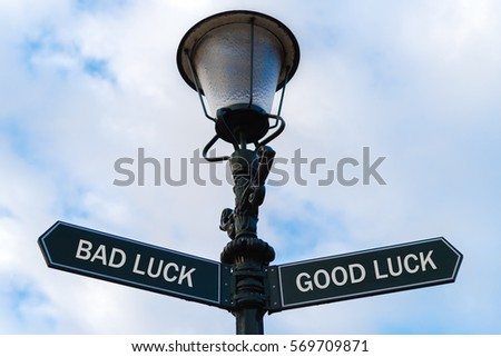 Street lighting pole with two opposite directional arrows over blue cloudy background. Bad Luck versus Good Luck concept. #569709871
