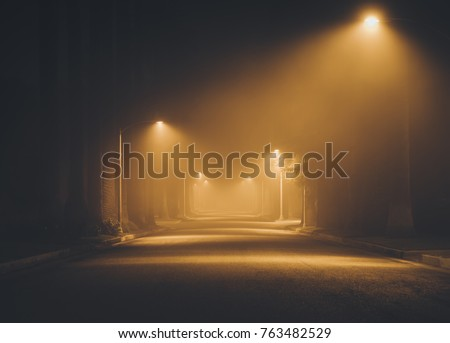 Street lights foggy misty night lamp post lanterns deserted road.