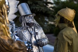 street man statue in a metal suit with a cylinder on his head