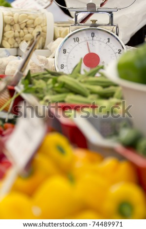 Street Market's table with its daily products with focus on a scale.