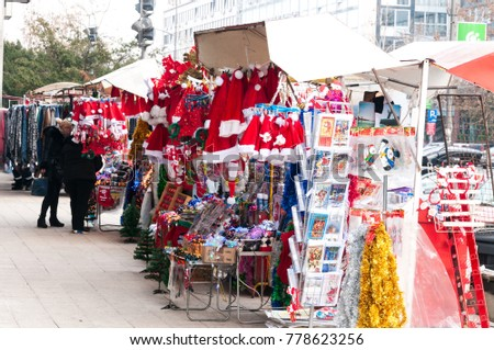 Street market vendors of Christmas and New Year holidays decorations and Santas hats. December - 20. 2017. Novi Sad, Serbia. Editorial image.