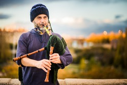 Street musician bagpiper playing traditional folk music in Spanish streets. Galician and Asturias culture historical music
