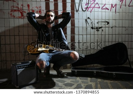 Street musician sitting and holding a guitar in the underpass. Vagrant lifestyle. Playing in the underpass to make a living. Unemployed musician. Future rock star. Horizontally framed shot.