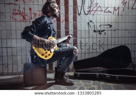 Street musician sitting on the amplifier and playing guitar in the underpass. Vagrant lifestyle. Playing in the underpass to make a living. Unemployed musician. Future rock star.