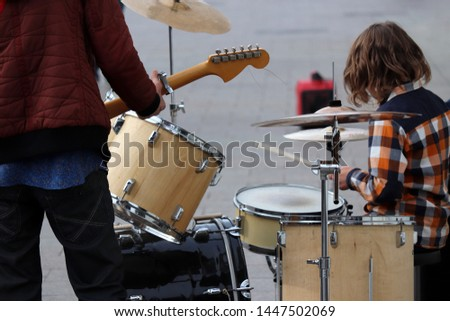 Street musicians play guitar and drums. Concert in a city, urban performers outdoor #1447502069