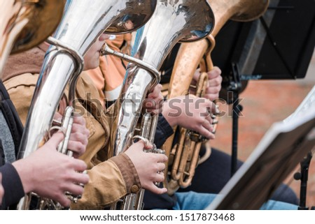 street musicians playing horn instruments in the fall. a row of street musicians playing wind instruments #1517873468