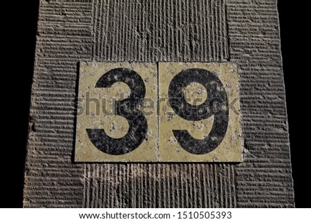 Street number. Number 39. Engraved numbers in black on a stone wall.