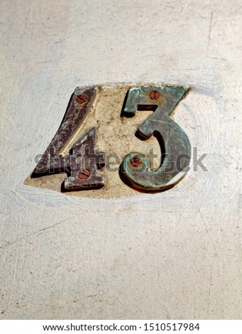 Street number. Number 43. Numbers of gilded metal on white wall.