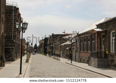 Street of the ancient city of Gyumri in Armenia, stretching forward, with old houses and a paved road