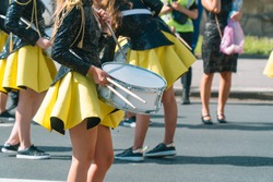 Street performance of festive march of drummers girls in yellow black costumes on city street. Street music concept
