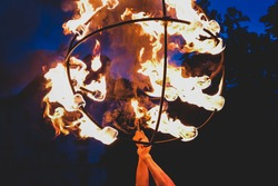 Street performer holds a show with ball of fire at night